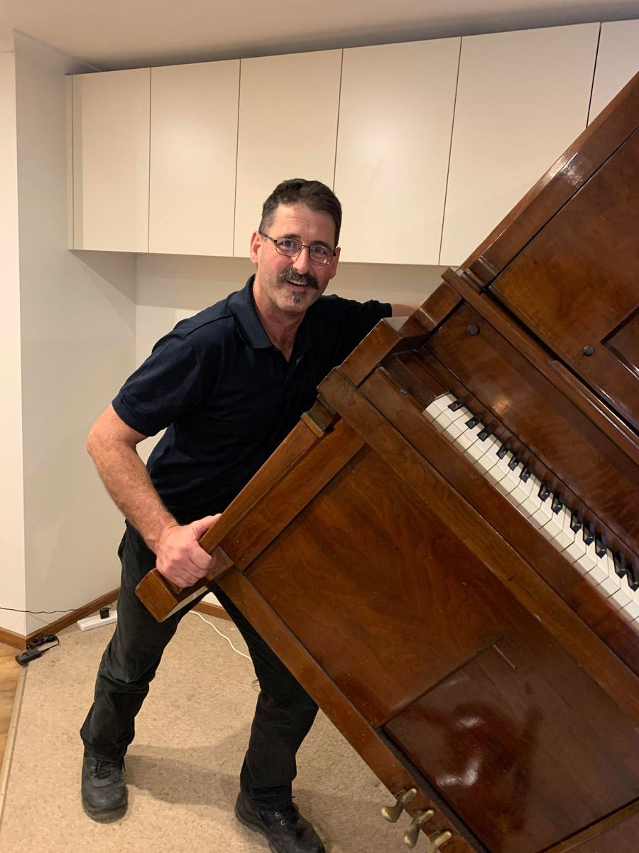 Piano mover man moving a piano in Melbourne, Victoria